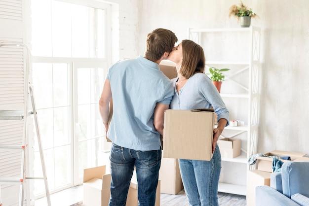 外に移動するために荷造りしながらロマンチックなカップルがお互いにキス 無料写真