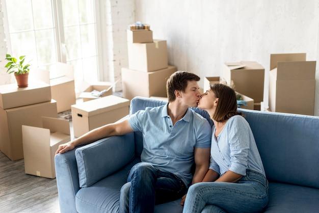 Романтическая пара целуется на диване, собираясь съехать Бесплатные Фотографии