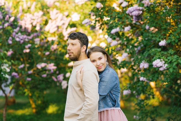 Premium Photo Romantic Couple In Love Embrace In The Spring In A Blooming Lilac Garden