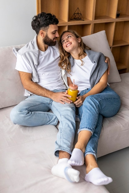 Romantic couple on the sofa at home having juice Free Photo