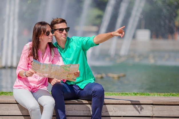 Romantic couple together with city map outdoors. happy lovers enjoying cityscape with famous landmarks. Premium Photo