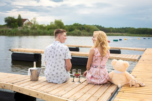 Romantic date surprise. young guy and a girl on a wooden pier. Premium Photo