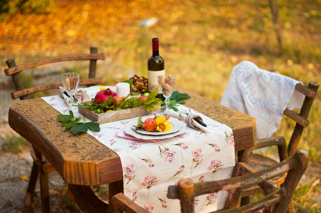 Romantic dinner in the autumn garden, table setting for a nice dinner. wine, fruit, pomegranate and flowers. picnic in the open air. Premium Photo