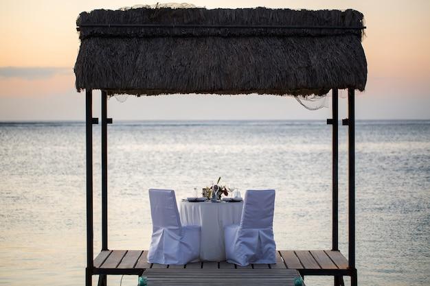 Романтический ужин на пляже на закате Premium Фотографии