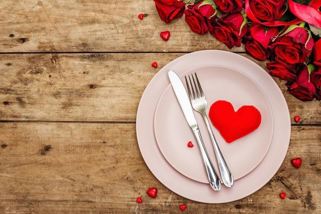 ロマンチックなディナーテーブル。バレンタインや母の日、結婚式のカトラリーの愛のコンセプト。新鮮なバーガンディのバラの花束、ヴィンテージの木の板の背景 Premium写真
