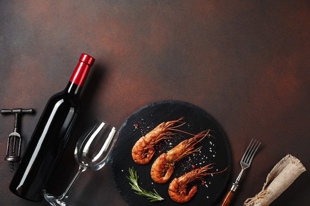 Romantic dinner with heart-shaped shrimps and wine on a brown background. top view with copy space Premium Photo