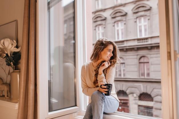 Modello femminile romantico di buon umore guardando la strada, seduto sul davanzale Foto Gratuite