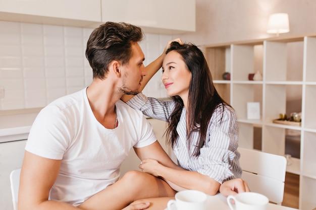Романтическая женская модель с прямыми волосами, с нежностью смотрящая на мужа после завтрака Бесплатные Фотографии