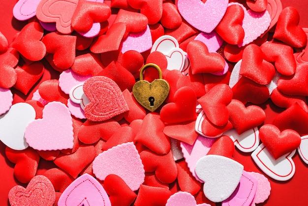 赤いハートに囲まれた愛の南京錠で、ロマンチックなフラットレイ。 Premium写真