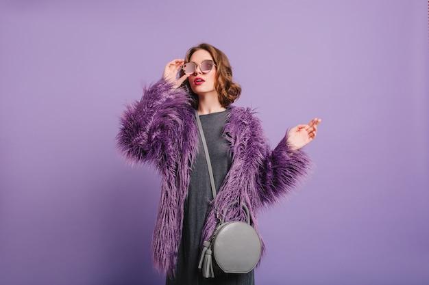トレンディなサングラスを通して見ている柔らかいふわふわのジャケットのロマンチックな女の子 無料写真