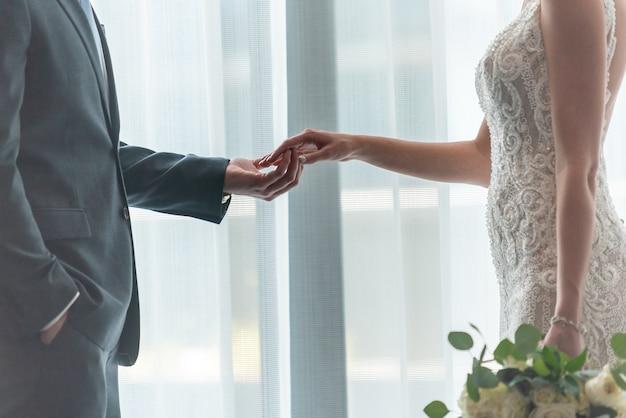 Романтический жених и невеста, взявшись за руки, стоя у окна Бесплатные Фотографии