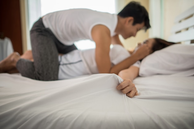 Romantic happy couple in bed enjoying sensual foreplay. Free Photo