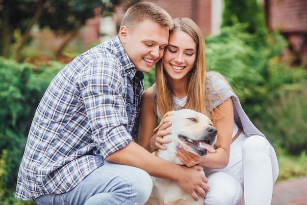 Романтическая счастливая семья в любви, наслаждаясь временем с лабрадором на природе. счастливая пара, лаская их желтый лабрадор. Premium Фотографии