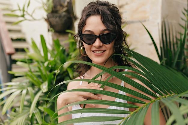Romantica donna felice con i capelli biondi corti ha chiuso gli occhi e godersi le vacanze in una calda giornata estiva sull'isola sul muro di piante esotiche Foto Gratuite