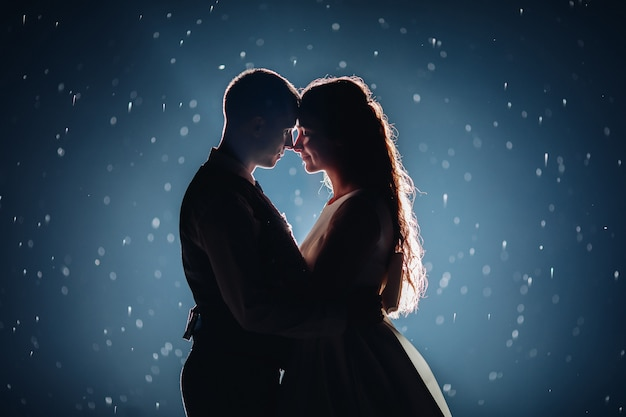 Romantica coppia appena sposata che abbraccia faccia a faccia su sfondo scuro illuminato con scintillii luminosi intorno. Foto Gratuite