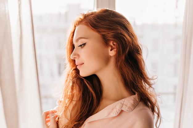 自宅でポーズをとるロマンチックな長髪の女性。物思いにふける魅力的な生姜少女の肖像画。 無料写真