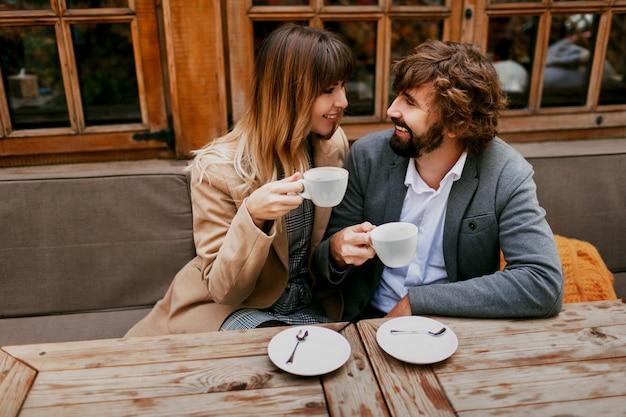 カフェに座って、コーヒーを飲みながら、会話をしながら、お互いに過ごす時間を楽しんでいる優雅なカップルのロマンチックな瞬間。 無料写真