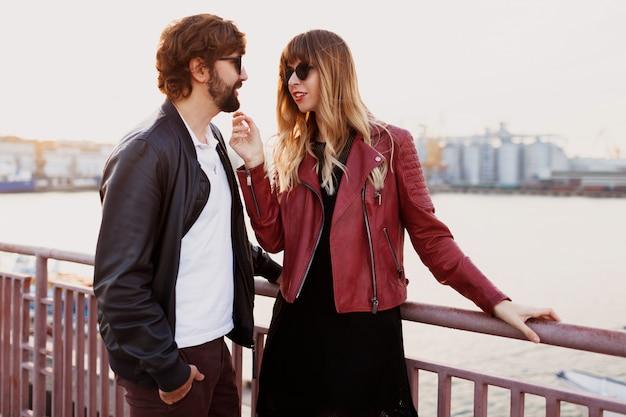 Романтические моменты стильной влюбленной пары, которая разговаривает и наслаждается временем, проведенным друг с другом. красивый мужчина с женой гуляют по мосту. Бесплатные Фотографии