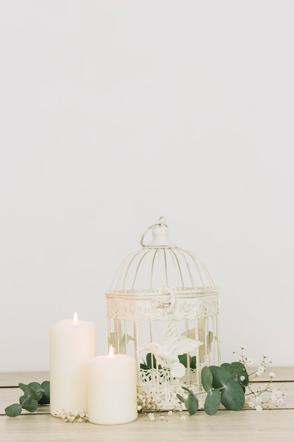 Romantic ornaments with candles and cage Free Photo