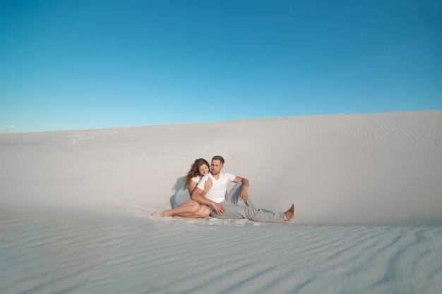 Romantic pair sit on white sand and huggins, in desert Premium Photo
