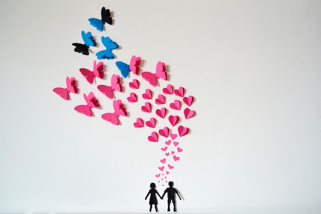 Romantic paper couple with hearts and butterflies flying Free Photo
