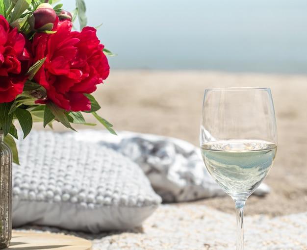 바다로 꽃과 샴페인 잔과 함께 낭만적 인 피크닉. 휴일의 개념. 무료 사진