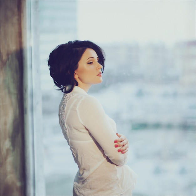 Romantic portrait of a beautiful young brunette in white shirt staying by the window Premium Photo