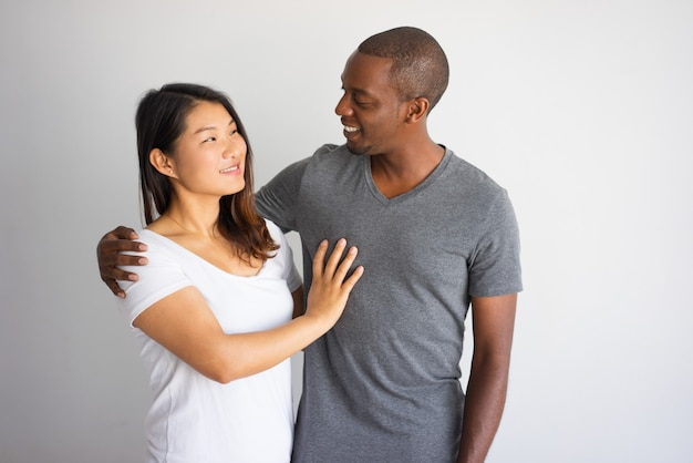 Romantic portrait of interracial couple smiling to each other. Free Photo