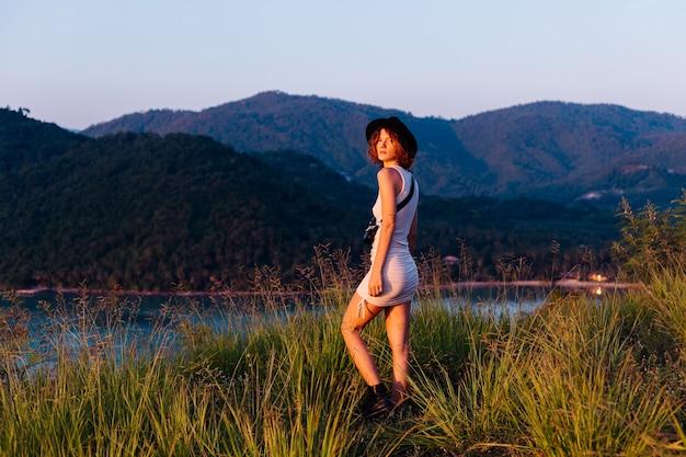 Ritratto romantico di giovane donna caucasica in abito estivo godendo di relax nel parco sulla montagna con incredibile vista sul mare tropicale femmina in vacanza viaggia in thailandia donna felice al tramonto Foto Gratuite