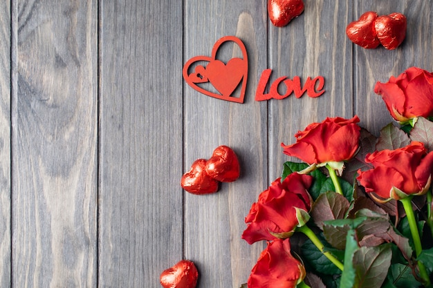 Romantic saint valentine wooden background card with bouquet of beatiful red roses and love lettering Premium Photo
