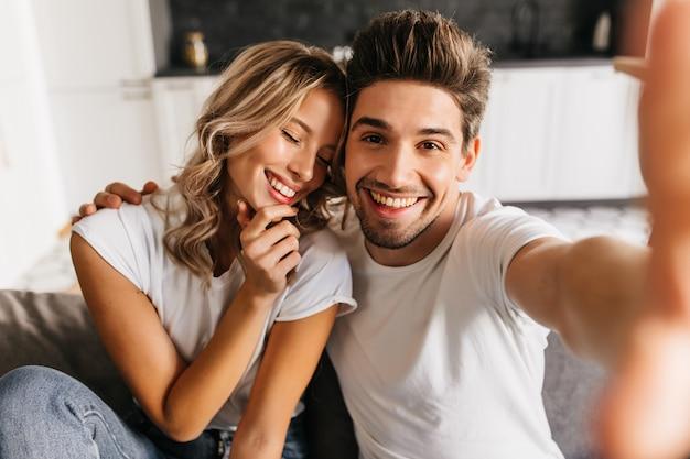 Coppie sorridenti romantiche che fanno selfie a casa seduto sul divano. l'uomo e la sua ragazza sorridono felicemente con gli occhi chiusi. Foto Gratuite