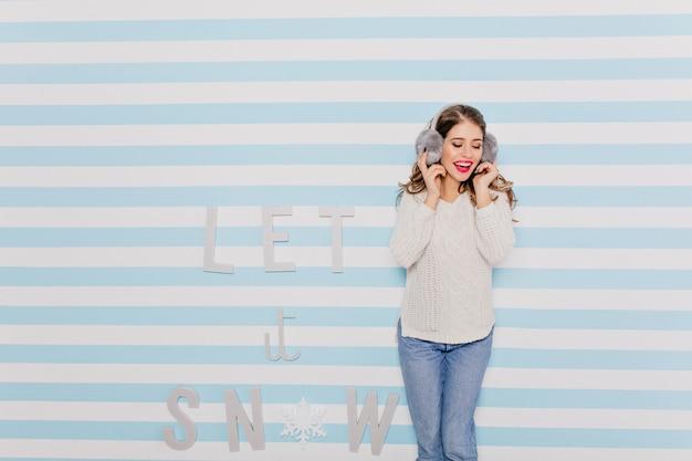 面白い大きなヘッドフォンで音楽を聴いているトレンディな冬の服装のロマンチックで甘い女性。明るい外観の長髪の少女の肖像画 無料写真