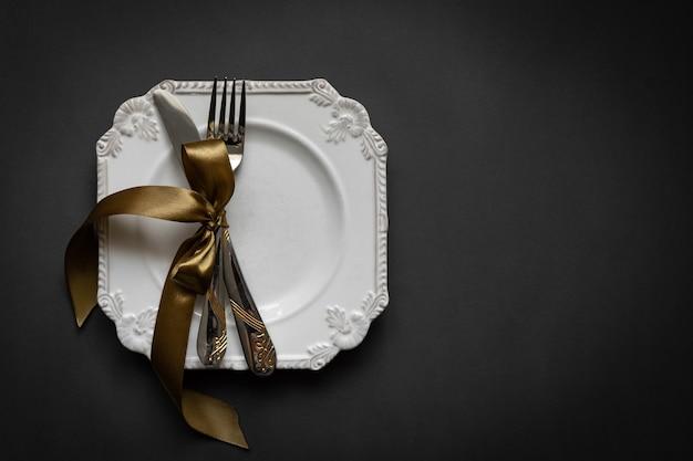 Романтическая установка tabble с лентой, тарелками, столовыми приборами на черном фоне. пустая тарелка. макет дизайна макета для вашего текста. романтическая концепция любви. скопируйте пространство. вид сверху. плоская планировка. Premium Фотографии