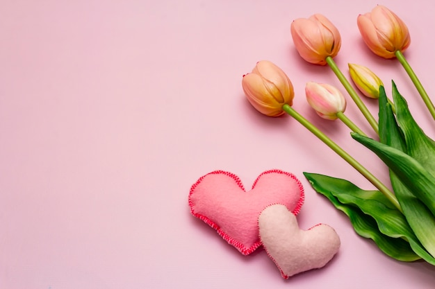 Romantic tulips bouquet on pink table with hearts. valentine concept Premium Photo