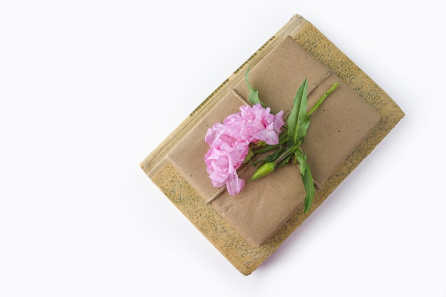 古い本とかわいいギフトボックスクラフト紙で包まれ、白地にピンクの花で飾られたロマンチックなヴィンテージの静物 Premium写真