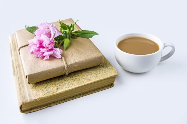 古い本、紅茶やコーヒーのカップ、クラフトペーパーで包まれ、白地にピンクの花で飾られたかなりのギフトボックスのロマンチックなヴィンテージの静物 Premium写真