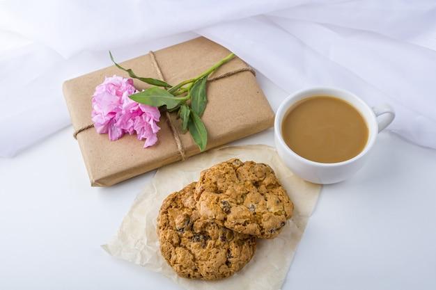 茶色のクラフトペーパーで包まれ、白地にピンクの花で飾られたかわいいギフトボックスのあるロマンチックなヴィンテージの静物 Premium写真