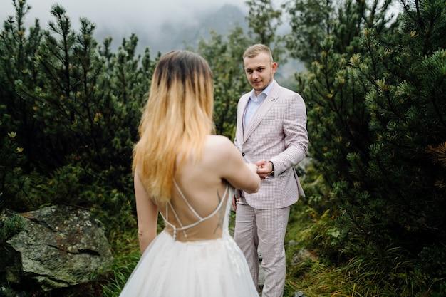 Romantic wedding couple in love standing of the sea eye lake in poland. tatra mountains. Free Photo