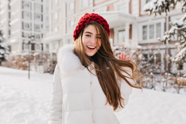赤いニット帽子のロマンチックな女性は、雪に覆われた通りで彼女の長い茶色の髪と遊ぶ。冬の休暇で歩き回って熱狂的なヨーロッパの女性モデルの屋外写真。 無料写真