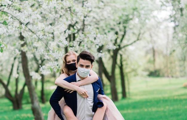 保護マスクを身に着けて一緒に時間を楽しんでいるロマンチックな若い美しいカップル Premium写真