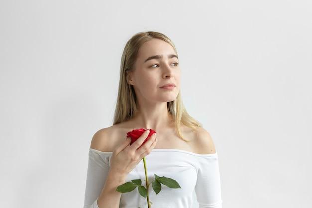 Романтичная молодая кавказская женщина в платье с открытыми плечами и длинными рукавами держит одну красную розу от парня на первом свидании, глядя в сторону с мечтательной загадочной улыбкой. любовь, страсть и романтика Бесплатные Фотографии