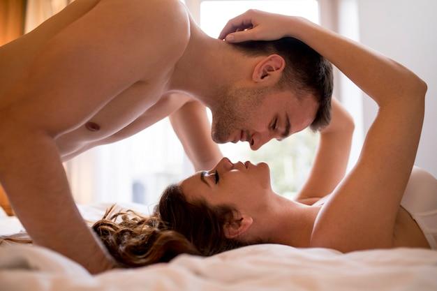 Романтическая молодая пара, лежа на кровати с телами в противоположных направлениях во время поцелуя Premium Фотографии