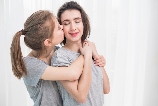 Romantic young lesbian couple standing against white curtain Free Photo