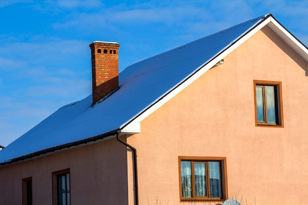 Roof of a new built house with nice window and chimney. Premium Photo