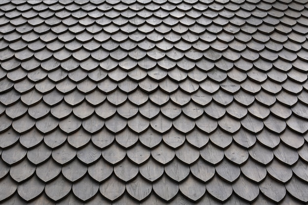 Roof with wooden petal tile texture, laid in smooth rows. Premium Photo