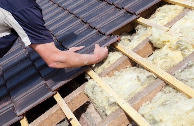 A roofer laying tile on the roof Premium Photo