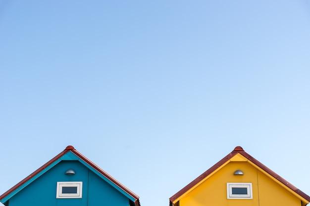 하늘에 Copyspace와 작은 파란색과 노란색 집의 지붕 무료 사진