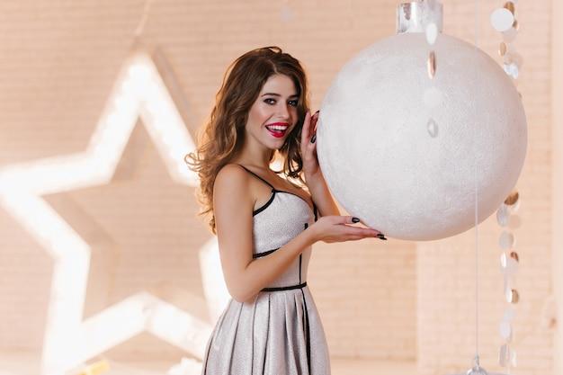 백라이트가있는 큰 별과 거대한 크리스마스 공, 아름다운 세련된 드레스를 입은 젊은 여성으로 장식 된 방 무료 사진