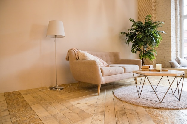 Room in a loft style. interior with sofa,coffee table and little tree. sofa with coffee table with a books and candles Premium Photo