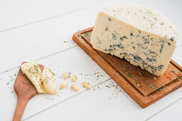 Roquefort cheese on wooden board with spatula on white table Free Photo